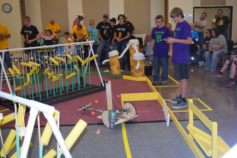 Peetz E.I.E.I.O. team member Charles Fehringer looks on, helping to guide Matthew Davis, as he tries to round up pigs with their robot during the Golden Plains BEST Robotics Challenge Saturday, Oct. 29, 2016.