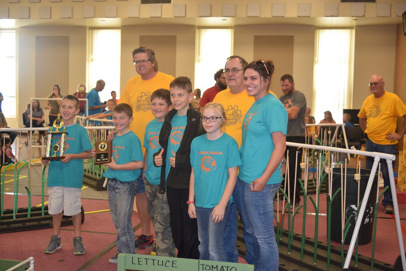 Larry Turner, back row right, hub director, and Mike Sullivan, back row left, assistant hub director, present the fourth place trophy for the Golden Plains BEST Robotics Challenge to the Peetz Robodogs team and their coach Jessica Schumacher. Team members include Lyle Schumacher, Brock Swedlund, Sadie Fehringer, Joe Fehringer and Mason Long.