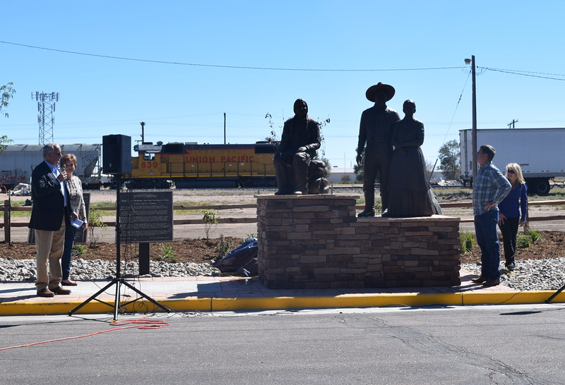 "A bronze sculpture depecting William Hadfield, Logan County's first settler, his wife, ""Aunt"" Charity Sanders Hadfield, and a contemporary of Hadfield's – a prairie Indian, is unveiled Saturday, Sept. 24, 2016. Helping to unveil the sculpture, located at Main and Front Street, were, from left; Don Saling, Sterling city manager and Rotary Club member; Cindy Johnson Horner, Reviewers and Rotary Club member; Pat Kennedy, the artist who created the sculpture; and Kim Sellers, executive director of the Logan County Chamber of Commerce."