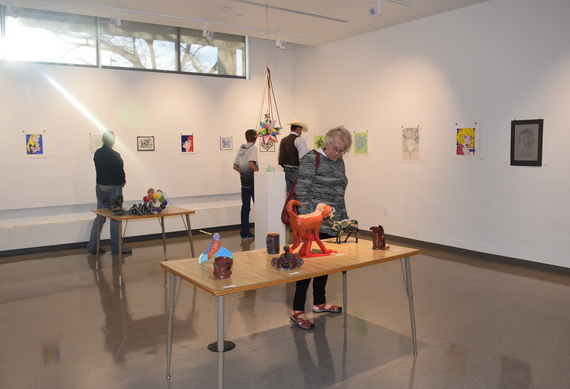 Guests look over artwork during a closing reception Thursday, April 14, 2016, for Northeastern Junior College's annual High Plains Secondary School Art Exhibit. The exhibit, which was held in the newly renovated Peter Youngers Art Galley inside E.S. French Hall, featured a variety of artwok created by local high school students.