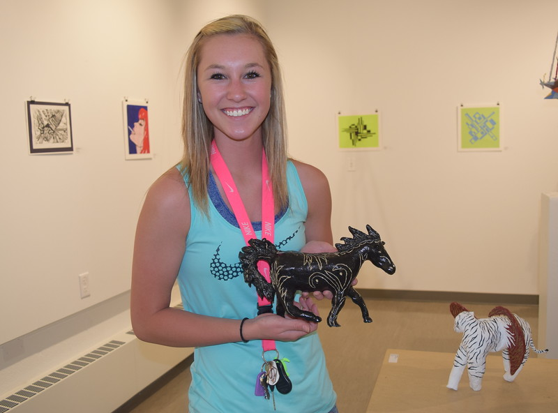 Taylor Shino, a senior at Sterling High School, holds up the ceramic horse she displayed in Northeastern Junior College's annual High Plains Secondary School Art Exhibit.