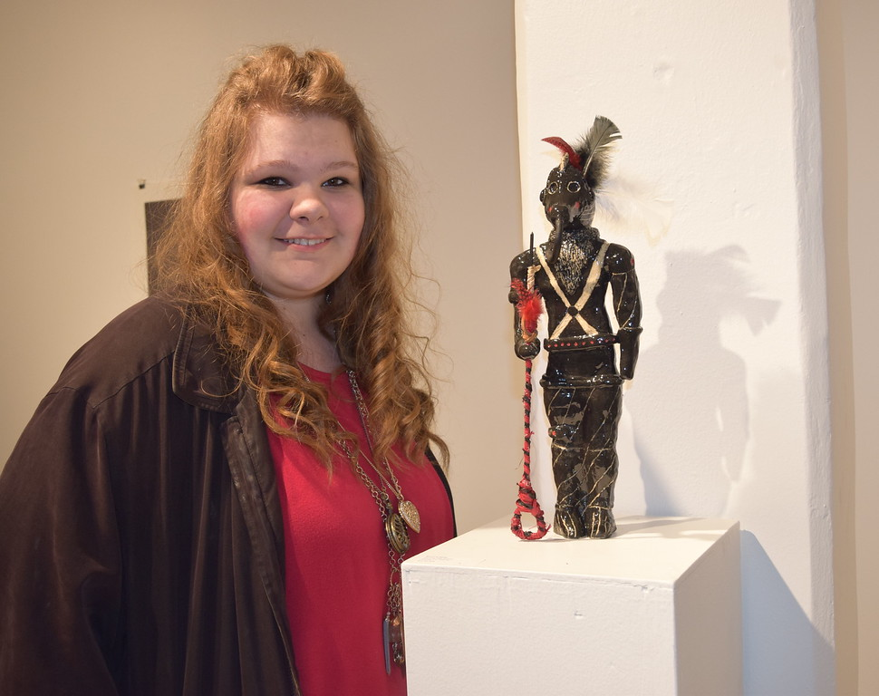 """Bryanna Bixby, a Sterling High School junior, poses for a photo next to the ceramic figure, """"Georgi the Warrior,"""" that she displayed in Northeastern Junior College's annual High Plains Secondary School Art Exhibit."""