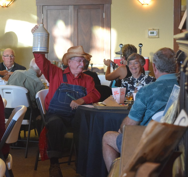 Curt Kimball, dressed as a bootlegger, raises up his whiskey jug in celebration, at Overland Trail Museum's History After Dark – Date Night at the Museum program on the 1920s Friday, June 23, 2017. Several guests dressed in 1920s attire for the program.