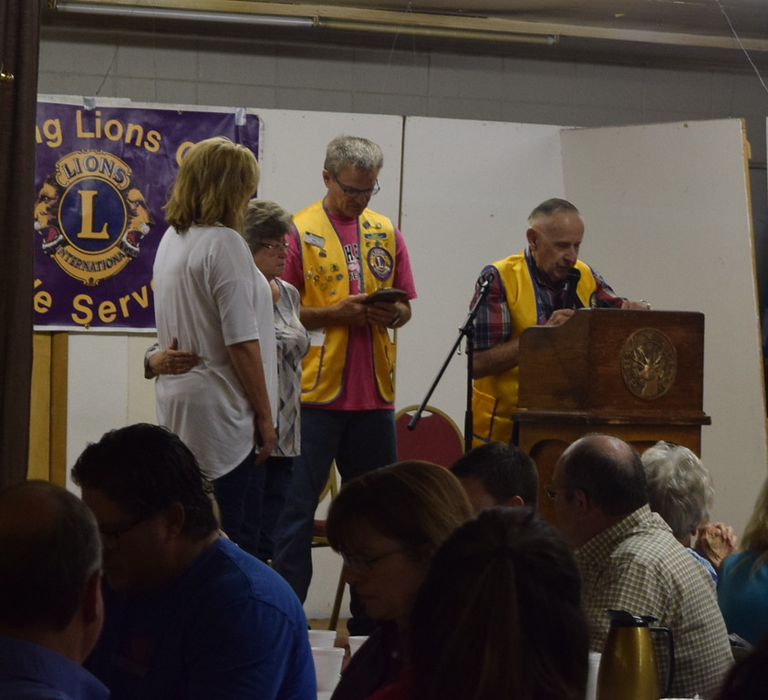 Lions Club members Jack Annan, right, and Dave Fast present a plaque to Logan County Fair Parade Marshal Linda Meisner and her late husband, Gene, at the Cowboy Breakfast Wednesday, Aug. 9, 2017.
