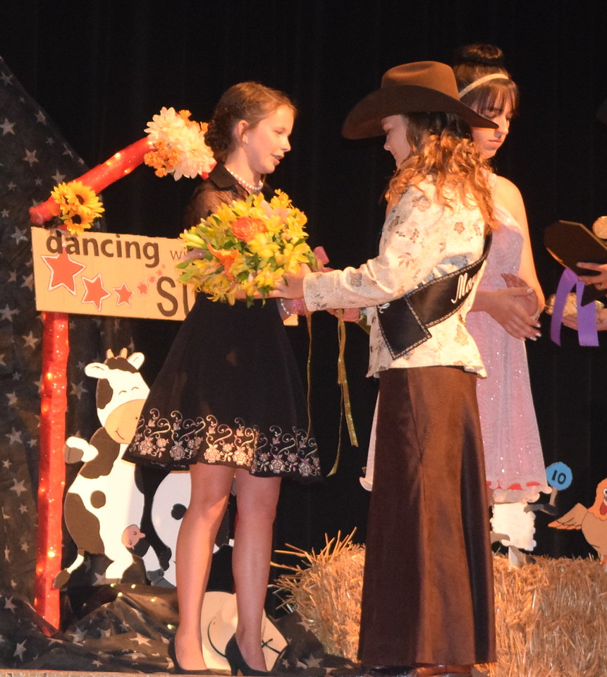 2017 Queen Contestant Morgan Duncan presents flowers to Aly Young, champion of the encore and senior divisions, during the Logan County Fair 4-H Fashion Revue Friday, Aug. 4, 2017.