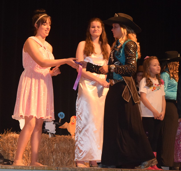 2017 Miss Rodeo Logan County McKaylin Schreiner presents a ribbon to encore division reserve champion Shelby Houser during the Logan County Fair 4-H Fashion Revue Friday, Aug. 4, 2017.