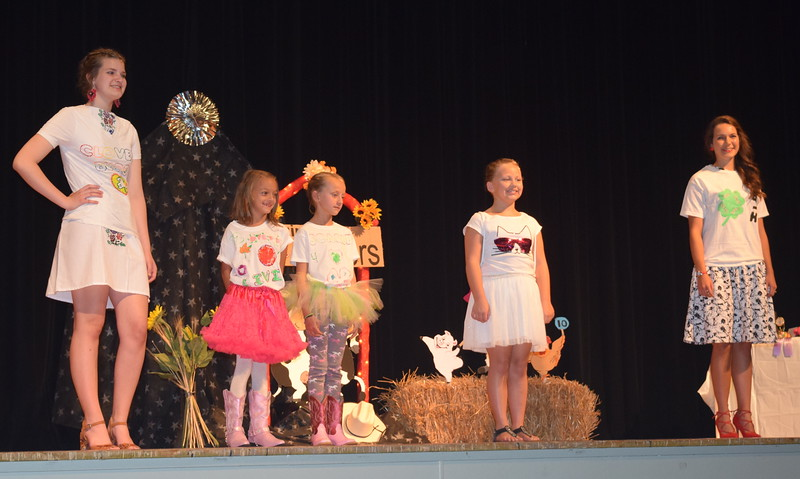 From left; Cloverbuds Olivia Ziegler, Scarlet Decker and Flliana Pelton model their outfits at the Logan County Fair 4-H Fashion Revue Friday, Aug. 4, 2017. Joining them are Cloverbud leaders Kathryn Lock, left, and Rachael Northup.