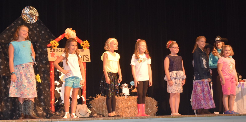 Participants in the junior division wait to hear the results for their division during the Logan County Fair 4-H Fashion Revue Friday, Aug. 4, 2017. From left; Mattea Pelton, Alexis Gentry, Natalie Adels, Ayla Baney, Savannah Taylor, Ashton Nichols and Ava Knight.
