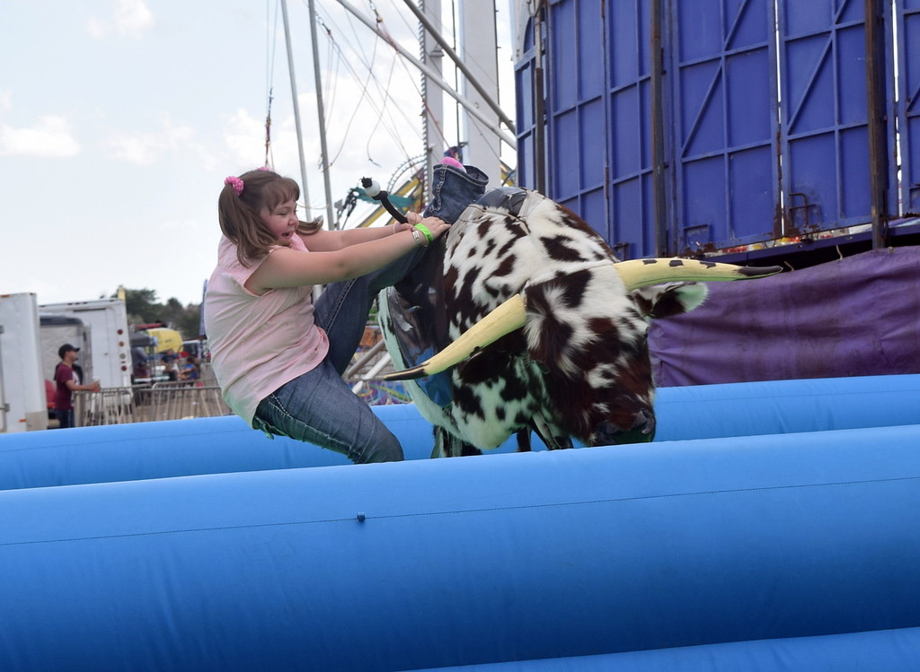 . A youngster gives it all she\'s got as she tries to hold on to a bucking broco at the Logan County Fair carnival Saturday, Aug. 12, 2017.