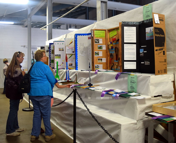 Visitors look over 4-H projects on display underneath the grandstands Wednesday, Aug. 9, 2017, at the Logan County Fair.