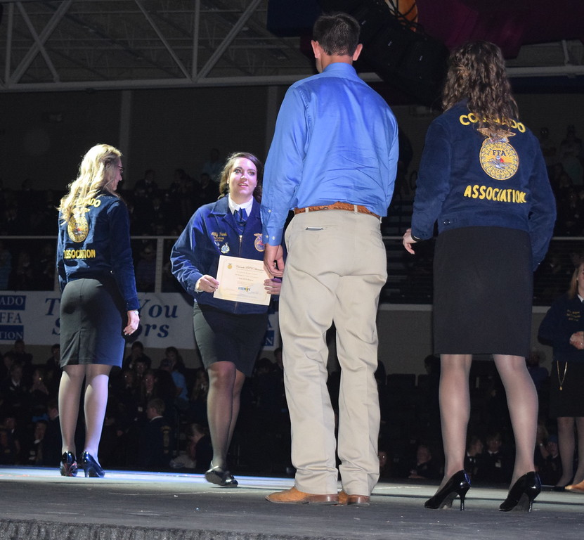 Ally Funk, of the New Raymer FFA chapter, walks to her adviser Kevin Schlabach after receiving her State FFA Degree during the Colorado FFA State Convention Wednesday, June 8, 2016. She was also recognized as a state proficiency winner in goat production for her Supervised Agricultural Experience (SAE).