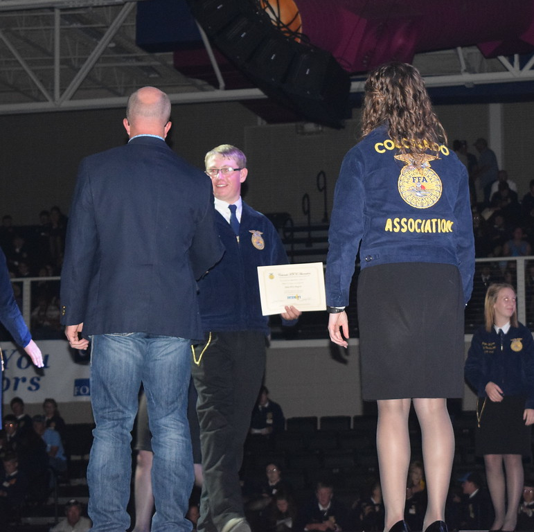 Adam Davis, of the Peetz FFA chapter, is congratulated by his adviser Mike Forster after receiving his State FFA Degree at the Colorado FFA State Convention Wednesday, June 8, 2016.