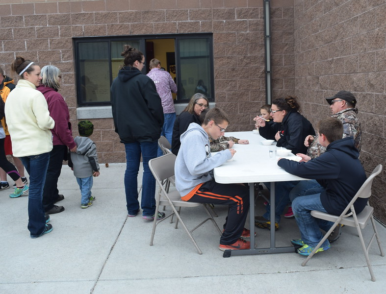 Students and families enjoy cheesy corn chowder at the football concession stand at one of the stations that was part of Merino High School and Elementary's Walking Dinner Thursday, April 28, 2016.