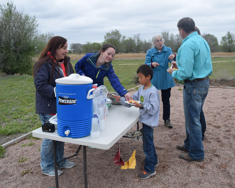 "Merino High School students dish out some ""Fabulous Fruit Salad"" to students and families at one of the stations that was part of the school's Walking Dinner Thursday, April 28, 2016."