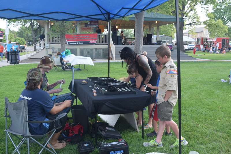 Concertgoers look over items for sale at the Sacred Manner booth during the July Jamz concert Friday, July 22, 2016.