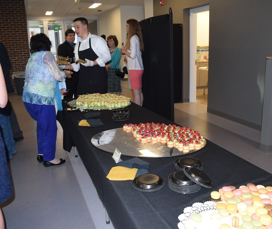 Guests enjoy Guests enjoy hors d'oeuvres in the atrium during the E.S. French grand re-opening celebration Saturday, April 2, 2016.