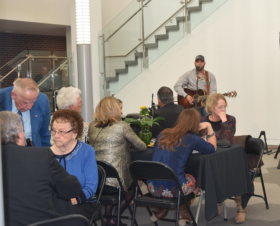 Guests enjoy cocktails and hors d'oeuvres while listening to a performance by Braydon Zink during the E.S. French grand re-opening celebration Saturday, April 2, 2016.