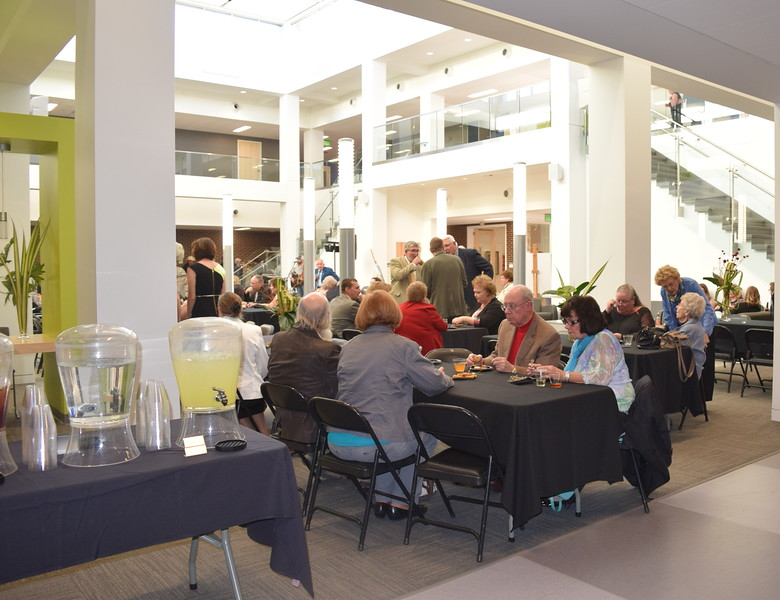 Guests enjoy cocktails and hors d'oeuvres in the atrium during the E.S. French grand re-opening celebration Saturday, April 2, 2016.