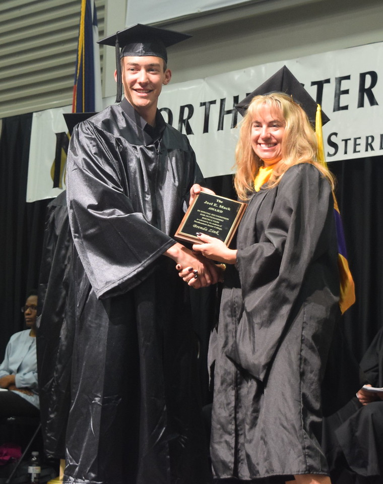 Garet Davis, Associate Student Government first vice president, presents the Joel E. Mack Award to Brenda Zink, chair of the health, science and math department, at Northeastern Junior College's commencement Friday, May 12, 2017.