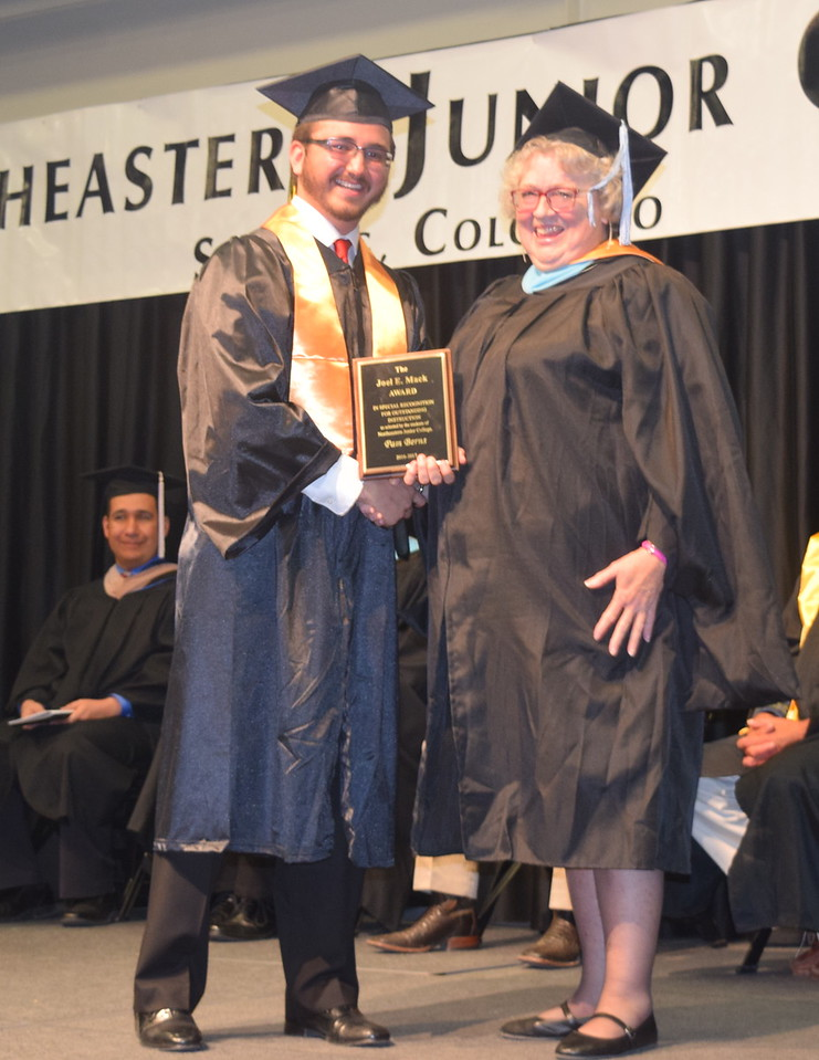 Christian Saunders, left, Associate Student Government president, presents the Joel E. Mack Award to English professor Pam Berns at Northeastern Junior College's commencement Friday, May 12, 2017.