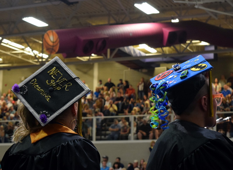 "Northeastern Junior College graduates decorated their caps in a variety of ways, from important reminders to ""never stop dreaming"" to Batman decorations."