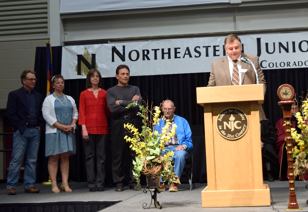 . Mark Kokes, president of the Northeastern Junior College Alumni Association board of directors, recognizes the association\'s 2018 Pride in Association Award recipient the Gabriel and Barbara Gertner Family during the commencement ceremony Friday, May 11, 2018.