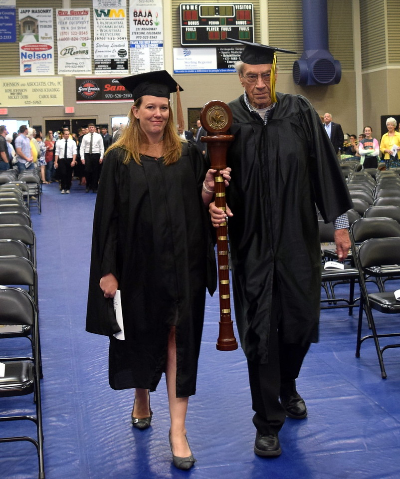 Alumni Mace Bearer Warren Brown, of the class of 1948, and Faculty/Staff Marshall Amanda Kerker lead graduates into the Bank of Colorado Event Center at the start of Northeastern Junior College's commencement ceremony Friday, May 11, 2018.