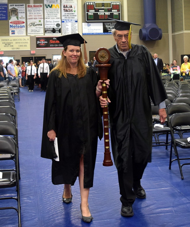 . Alumni Mace Bearer Warren Brown, of the class of 1948, and Faculty/Staff Marshall Amanda Kerker lead graduates into the Bank of Colorado Event Center at the start of Northeastern Junior College\'s commencement ceremony Friday, May 11, 2018.