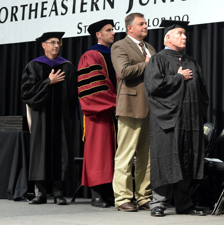 ". From left; Northeastern Junior College President Jay Lee; Dr. Landon Pirius, Colorado Community College System vice president; Mark Kokes, NJC Alumni Association president; and Fred Jackson, NJC Advisory Council member face the flag as the NJC Contemporary Choir performs the ""National Anthem\"" during the commencement ceremony Friday, May 11, 2018."