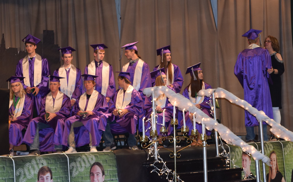 . Peetz High School Class of 2018 sponsor Traci Davenport flips Hunter White\'s tassel after he receives his diploma, while the other graduates look on during the school\'s commencement ceremony Sunday, May 13, 2018.