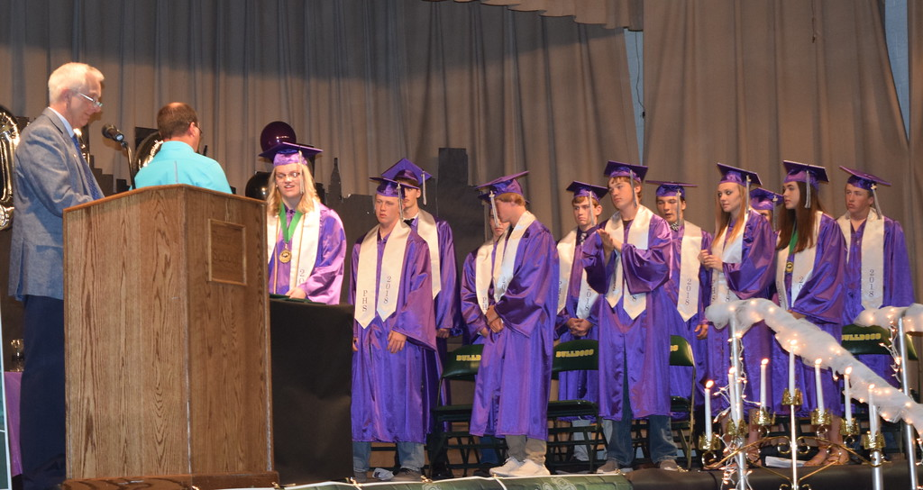 . Peetz School Board President Brad Segelke presents diplomas to the graduates as Superintendent Mark Collard calls their names during the school\'s commencement ceremony Sunday, May 13, 2018.