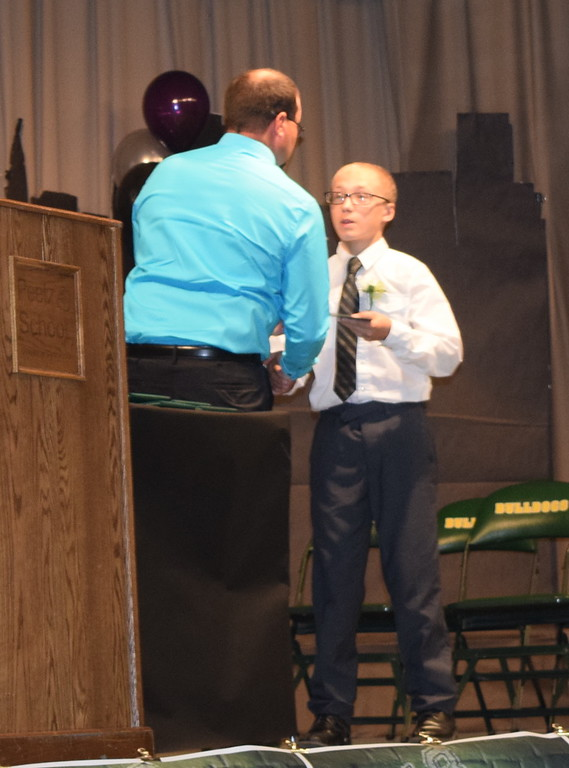 . Peetz School Board President Brad Segelke presents a diploma to eighth grader Michael Ramos during continuation exercises Sunday, May 13, 2018. He served as class representative for his two other absent classmates.
