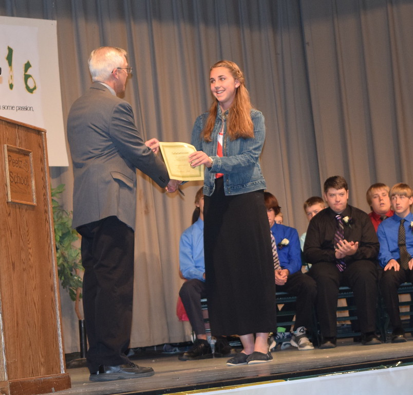 Superintendent Mark Collard presents a certificate to salutatorian Caroline Lindahl during Peetz School's continuation exercises Sunday, May 15, 2016.