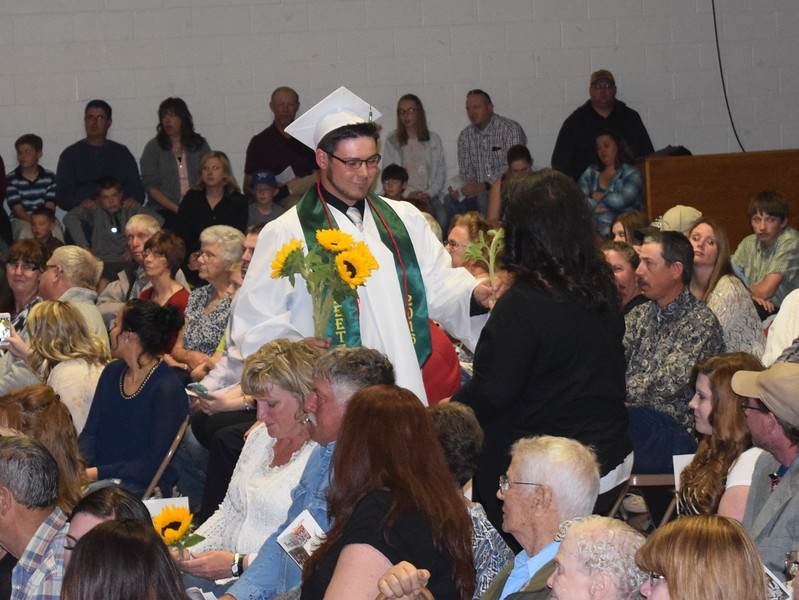 Garrin Cox gives sunflowers, the class flower, to family and friends during the Peetz High School commencement ceremony Sunday, May 15, 2016.