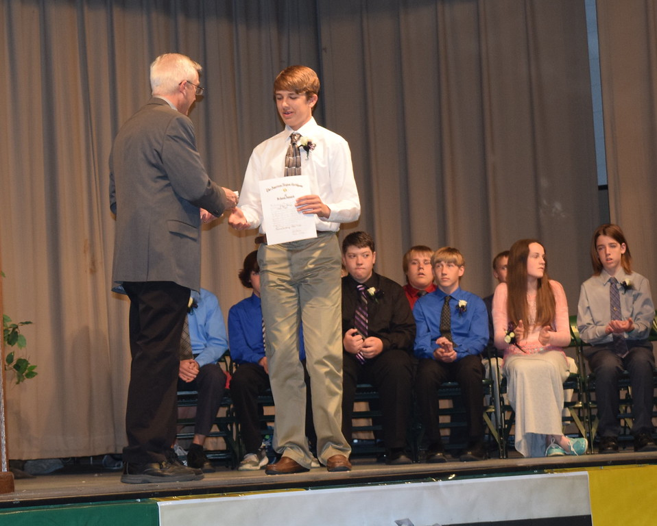 Superintendent Mark Collard presents an American Legion award to Ethan Ramey during Peetz School's continuation exercises Sunday, May 15, 2016. Rebecca Kennedy also received the award.