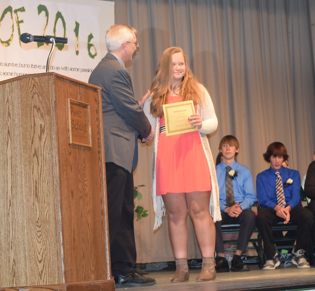 Superintendent Mark Collard presents a certificate to valedictorian Rebecca Kennedy during Peetz School's continuation exercises Sunday, May 15, 2016.