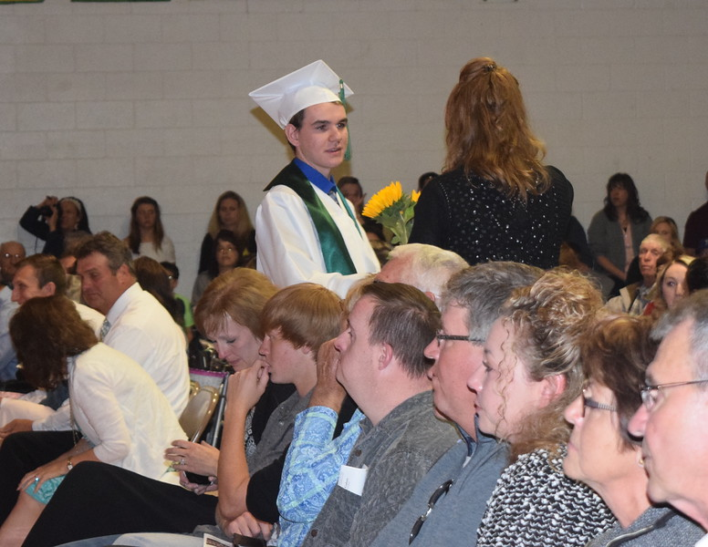 Colby Bellendir presents flowers to his family and friends during Peetz High School's commencement ceremony Sunday, May 15, 2016.