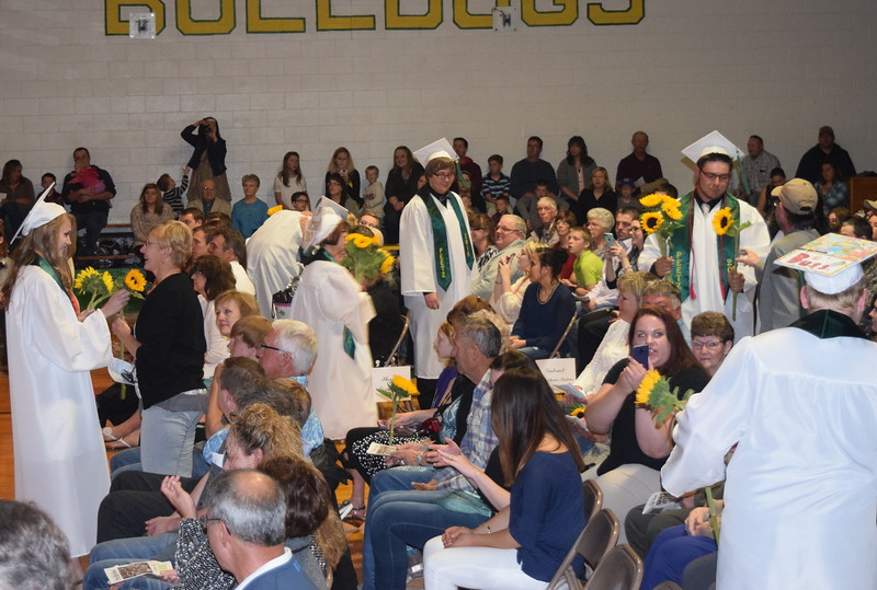 Graduates give sunflowers, the class flower, to family and friends, during the Peetz High School commencement ceremony Sunday, May 15, 2016.