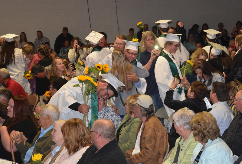 Graduates present sunflowers, the class flower, to family and friends during Peetz High School's commencement ceremony Sunday, May 15, 2016.