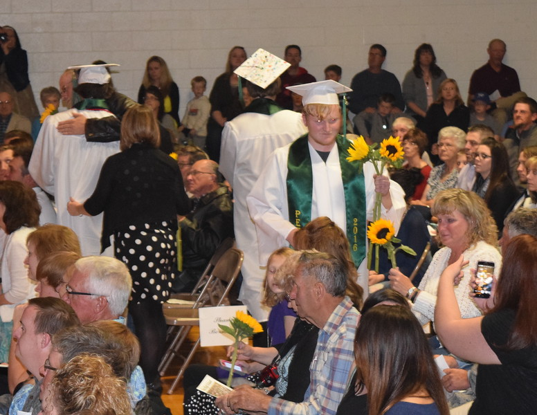 Graduates, including Jordan Buss, give sunflowers, the class flower, to their family and friends during Peetz High School's commencement ceremony Sunday, May 15, 2016.