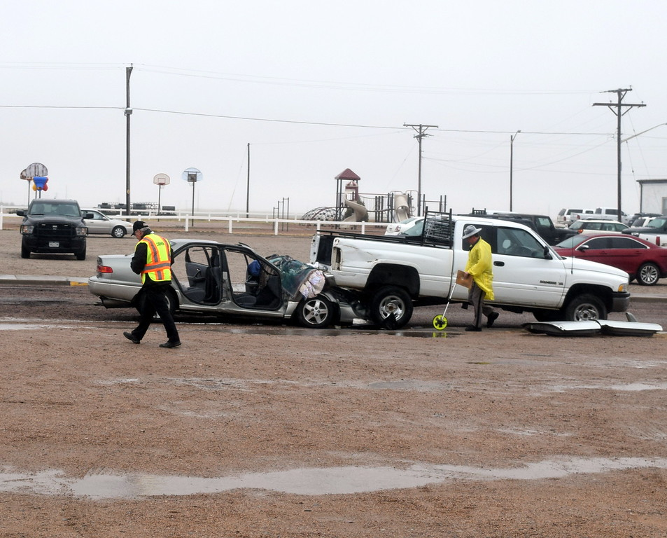 The county coroner and a Colorado State Patrol trooper investigate the scene of a mock car accident during an Every 15 Minutes program at Peetz School Tuesday, March 28, 2017.