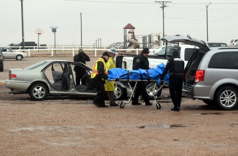 Officers from Colorado State Patrol and Logan County Sheriff's Office help the county coroner load the body of the victim who died in the mock car accident into the coroner's van to be taken to the morgue, during an Every 15 Minutes program at Peetz School Tuesday, March 28, 2017.