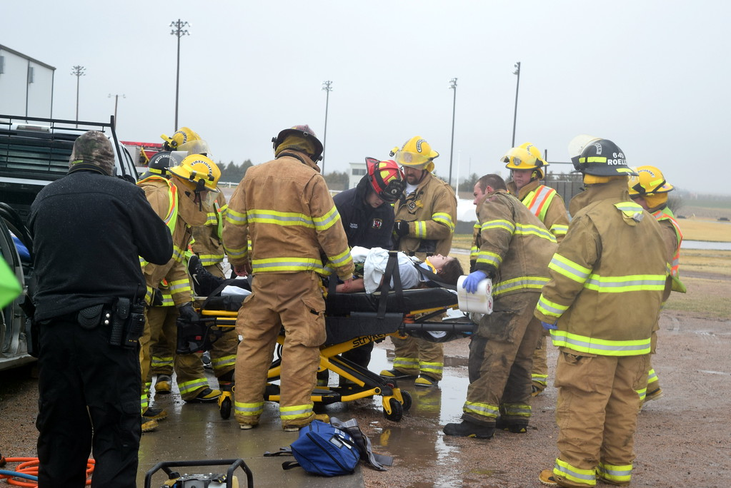 . Peetz Fire Department firefighters load a victim from the mock car accident onto a strecher to be transported by ambulance to the hospital during an Every 15 Minutes program at Peetz School Tuesday, March 28, 2017.