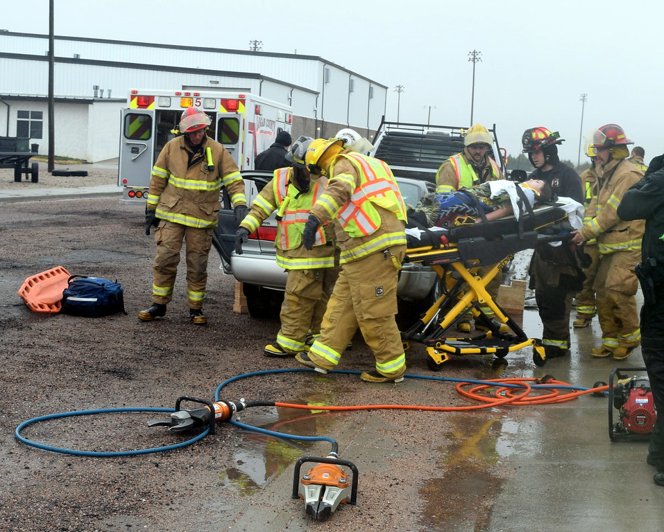 Firefighters from Peetz Fire Department wheel a victim injured in a mock car accident to the nearby ambulance during an Every 15 Minutes program at Peetz School Tuesday, March 28, 2017.