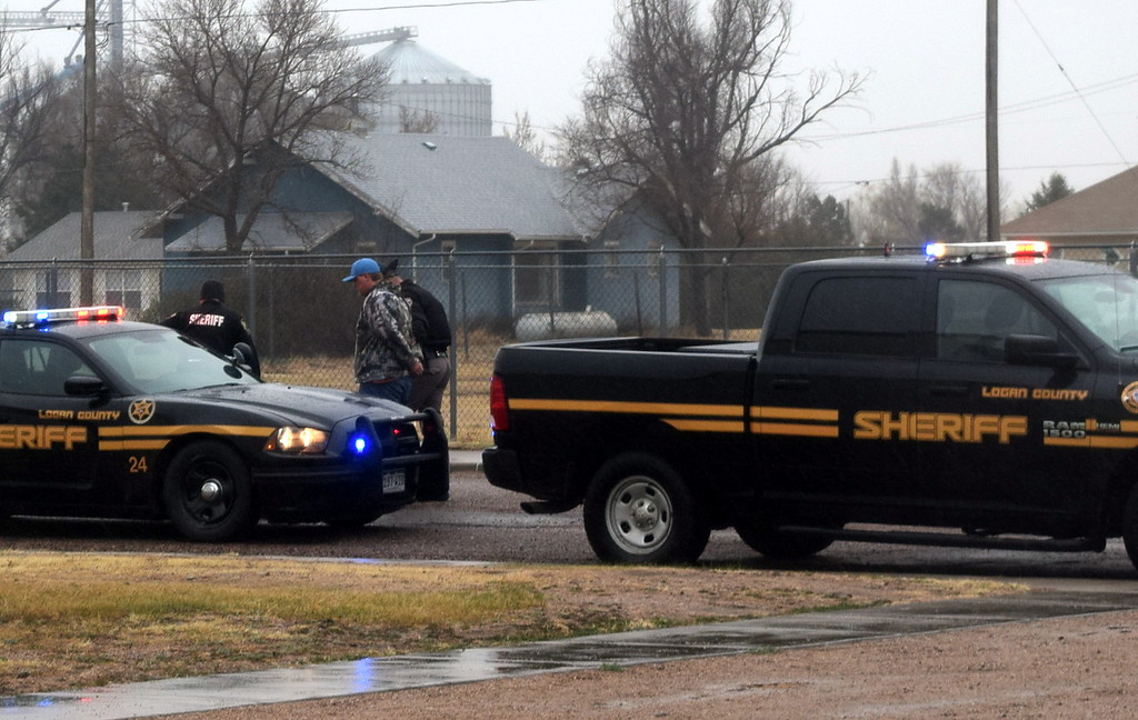 . A Colorado State Patrol officer leads the driver of the pickup to a Logan County Sheriff\'s Office vehicle after placing him under arrest for several charges, including careless driving, during a mock car accident that was part of the Every 15 Minutes program at Peetz School Tuesday, March 28, 2017.