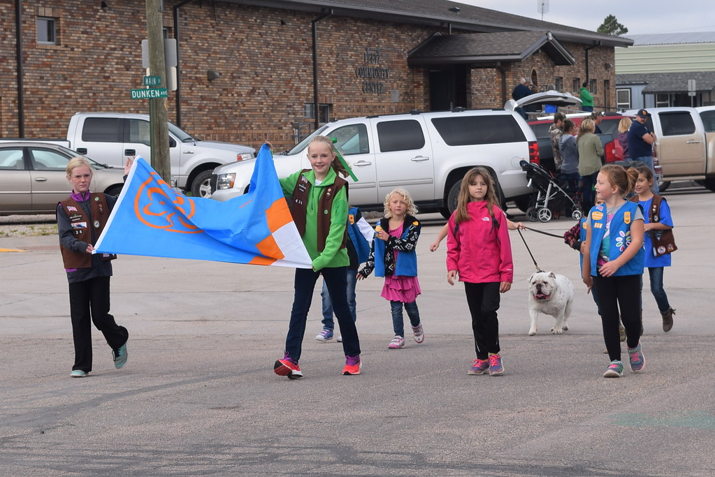 """. The Peetz Girl Scout troop, joined by Peetz School mascot Dozer, make their way down the parade route during the Peetz Sake Days \""""Still on the Hill\"""" Centennial Parade Saturday, Sept. 30, 2017"""