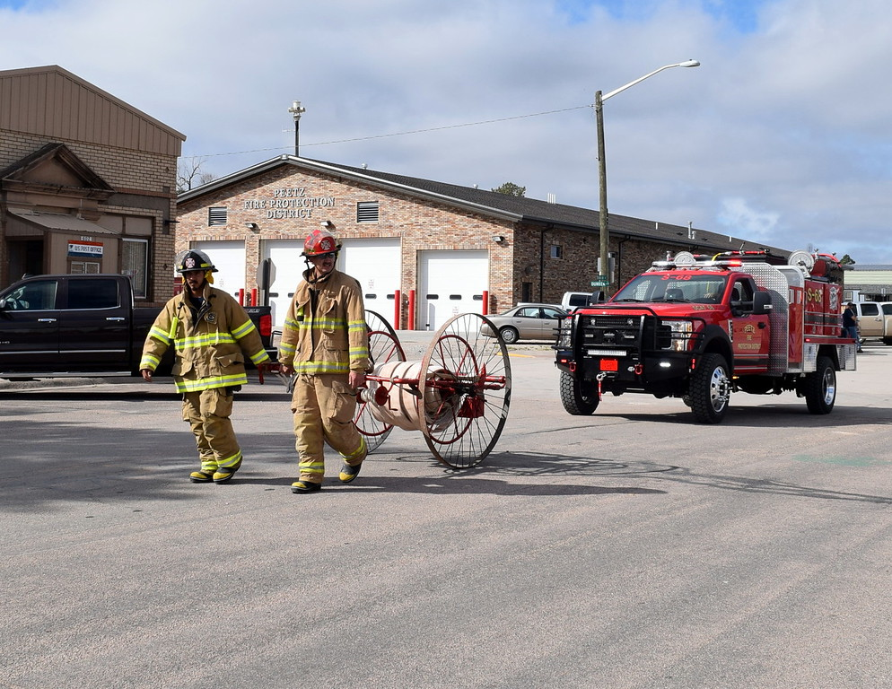 """. Members of the Peetz Volunteer Fire Department make their way down the parade route during the Peetz Sake Days \""""Still on the Hill\"""" Centennial Parade Saturday, Sept. 30, 2017."""