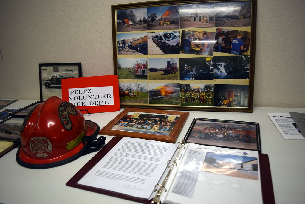 """. A firefighter\'s help sits on display with photographs and information about Peetz Volunteer Fire Department at Peetz Sake Days \""""Still on the Hill\"""" Centennial Celebration Saturday, Sept. 30, 2017."""