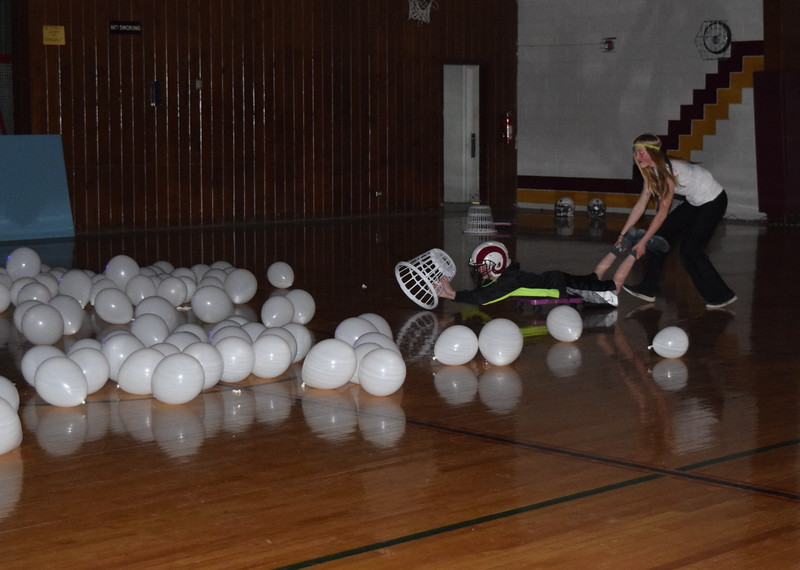 A contestant tries to gather balloons in a game of Human Hungry, Hungry Hippo during Merino Jr./Sr. High School's Neon Glow Energizer Afternoon Wednesday, Feb. 10, 2016.