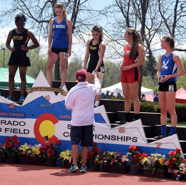 Caliche's Kayla Zink receives her medal for placing in the 100 meter dash.
